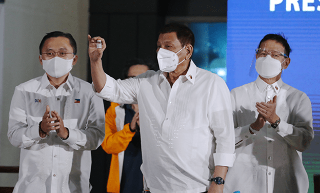 President Rodrigo Duterte holds a vial of the AstraZeneca vaccine,